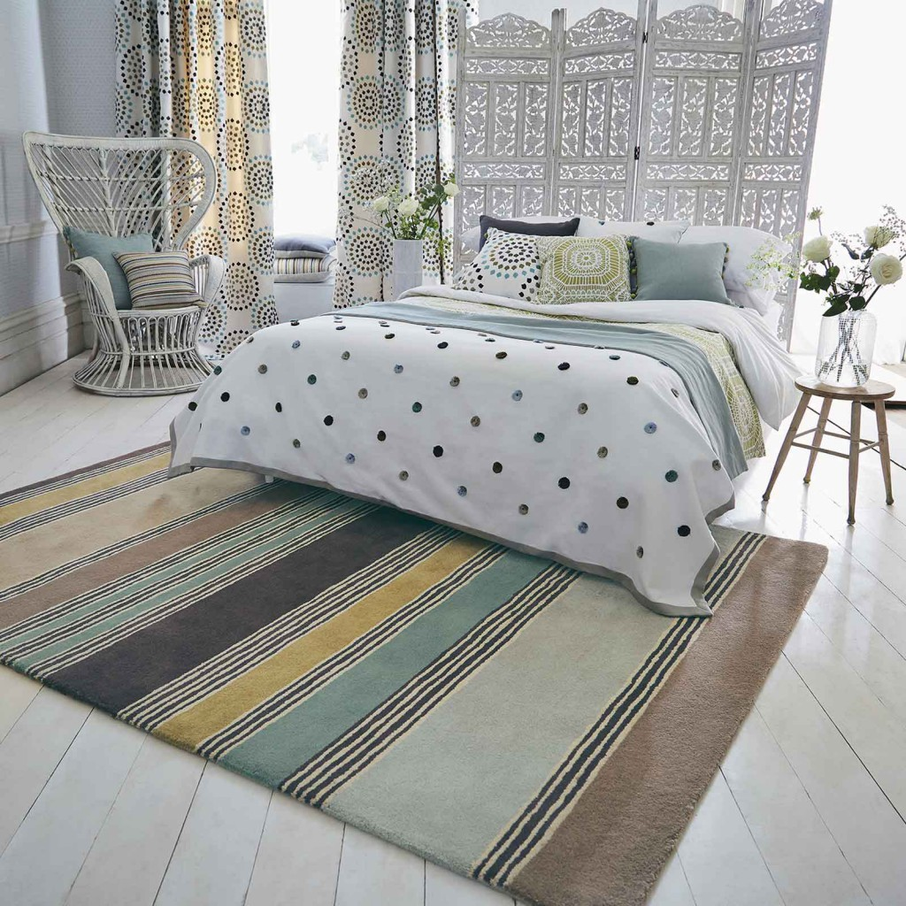 Designer rug brand Harlequin with a soft colour scheme fills a bedroom with stripy rug on the floor