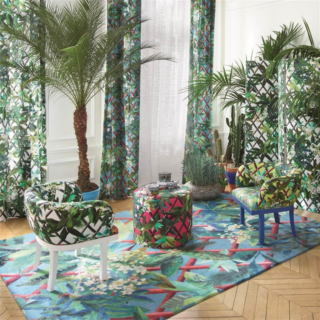 A Christian Lacroix designer rug brand inside a modern living room filled with indoor tropical plants