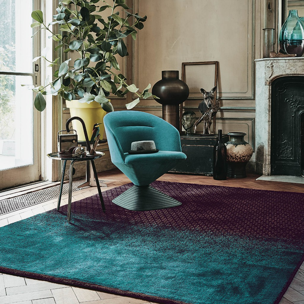 Designer rug brand Ted Baker with a bright teal and purple geometric rug surrounded by antiques
