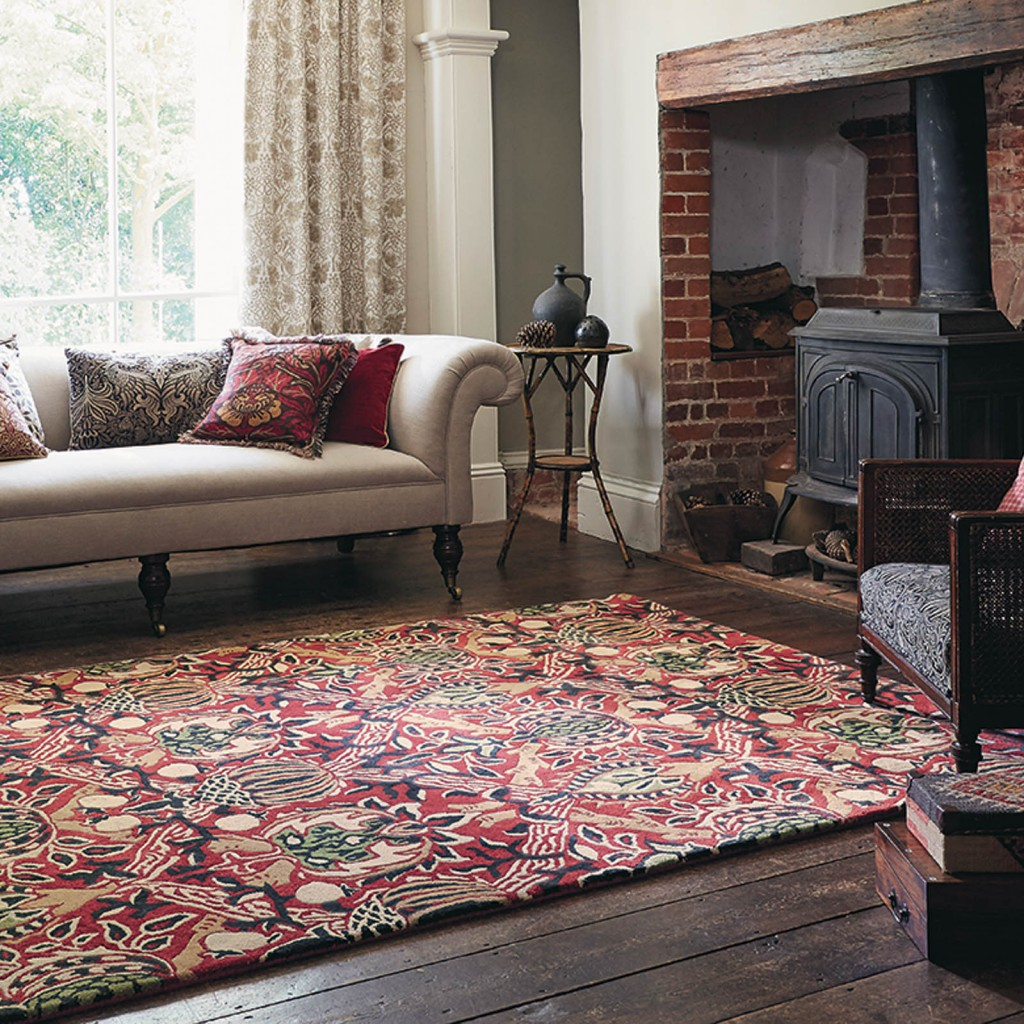 An old living room where a red paisley rug sits at its centre designer rug brand Morris & Co