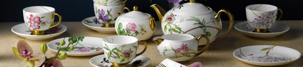 a wedgwood flowery tea set on a brown flecked table next to an orchid flower