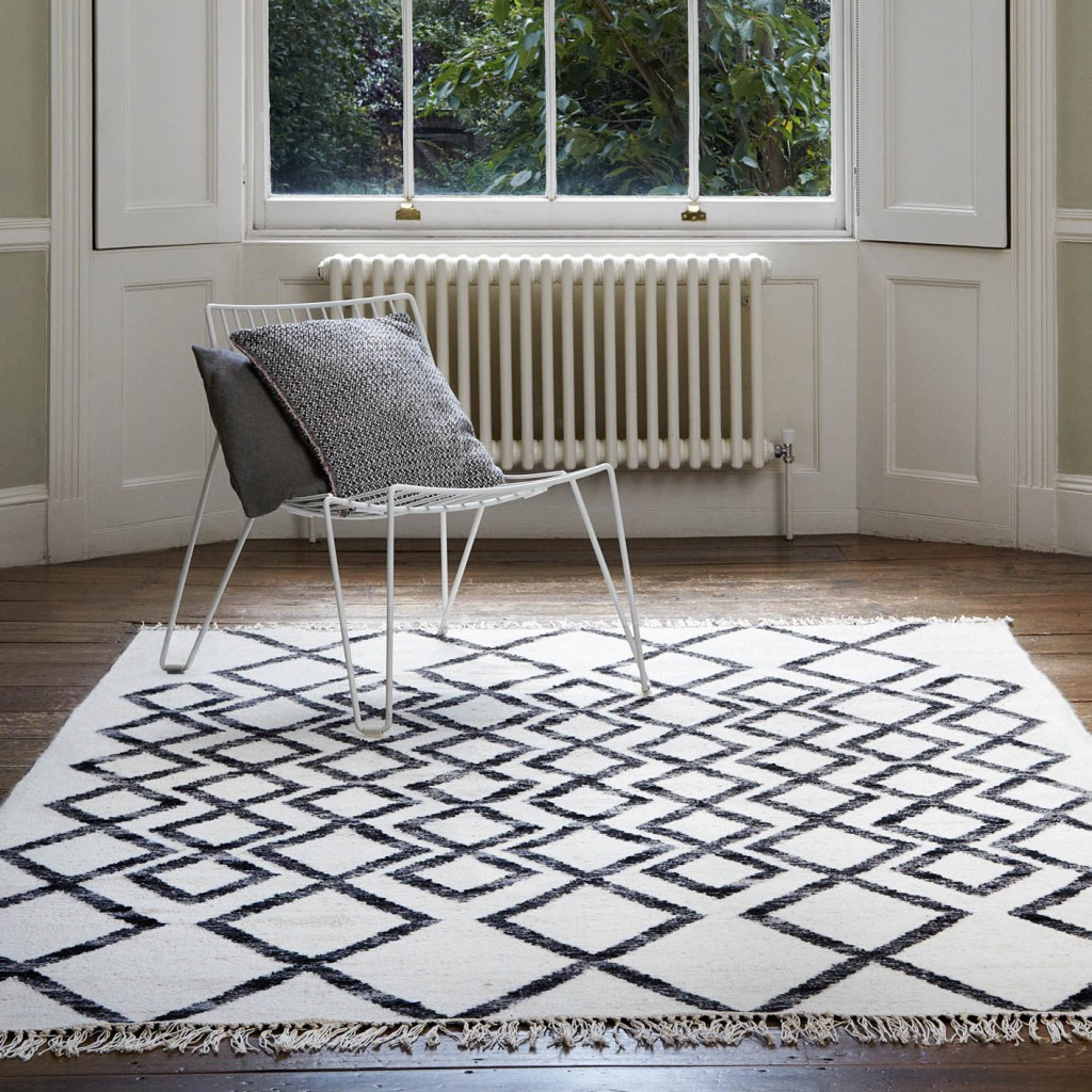 A modern living room with a geometric Scandinavian rug underneath a white chair