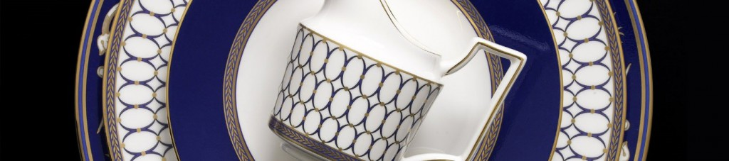 a milk jug placed on top of layered wedgwood plates with navy and gold designs on a black background