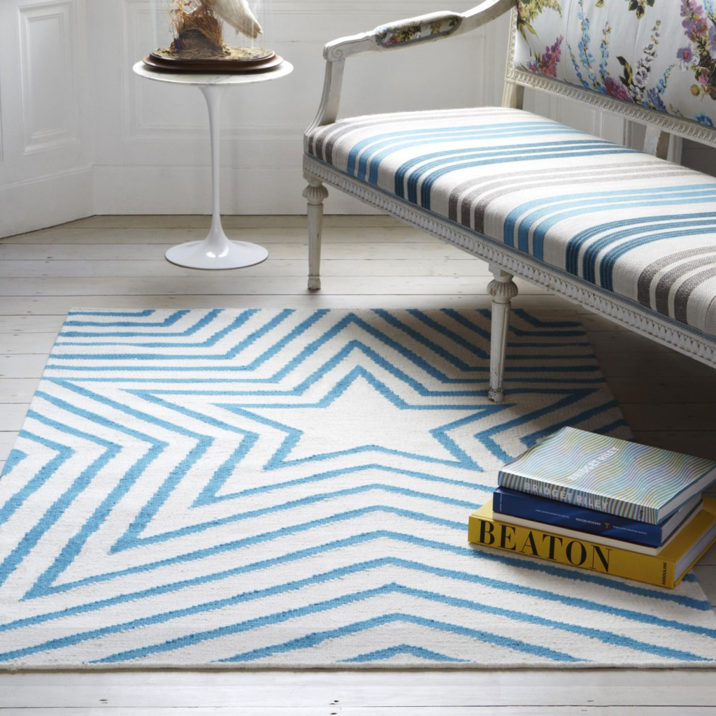 Blue and white star rug sits against a white wooden floor in a living room
