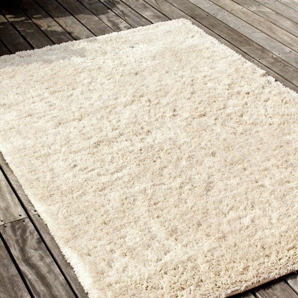 A plush, fluffy like shaggy pile Massimo rug, with a cream coloured background against wooden flooring
