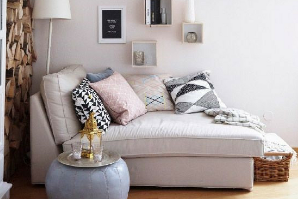 A large white coloured room with wall shelves with a large white lamp and a sofa bed covered in multiple cushions on a wooden floor with a bean bag table