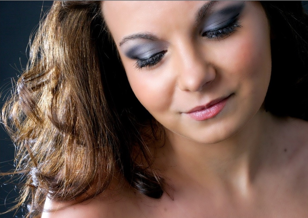 A close up portraiture photography shot of a smiling woman glancing downwards wearing smokey make up and rose coloured lipstick