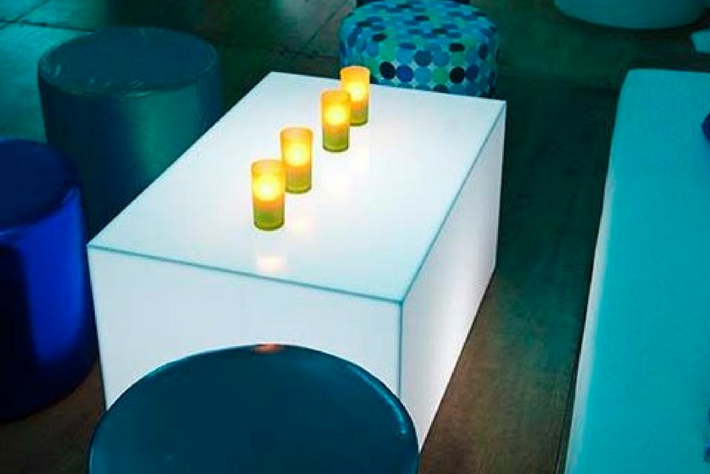 A light blue room with blue furniture including a blue sofa, blue stools and a white light table with four yellow candles
