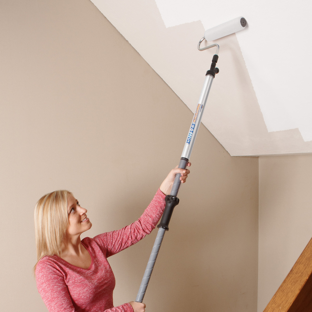 a woman holding a roller extension while she paints the ceiling beige