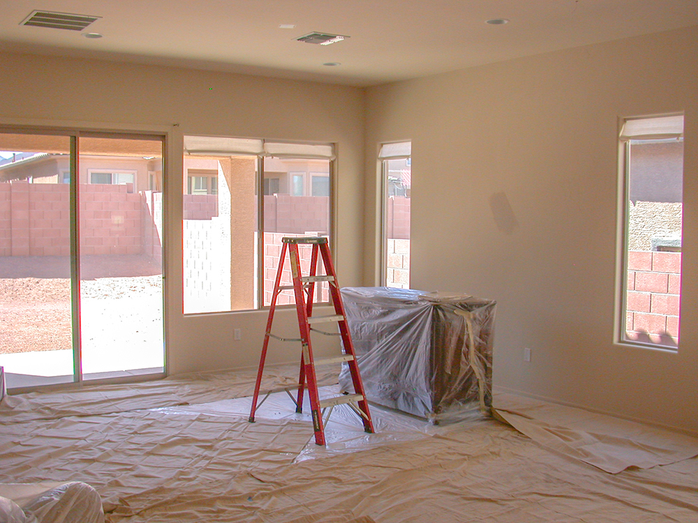 how to paint a room bright room covered in canvas for painting and a red ladder