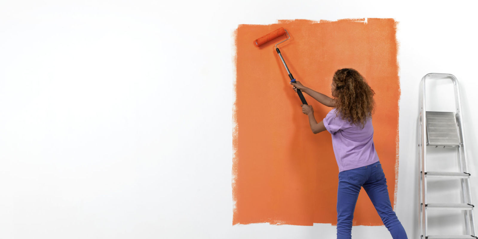 how to paint a wall using a with roller technique with a woman demonstrating with orange paint