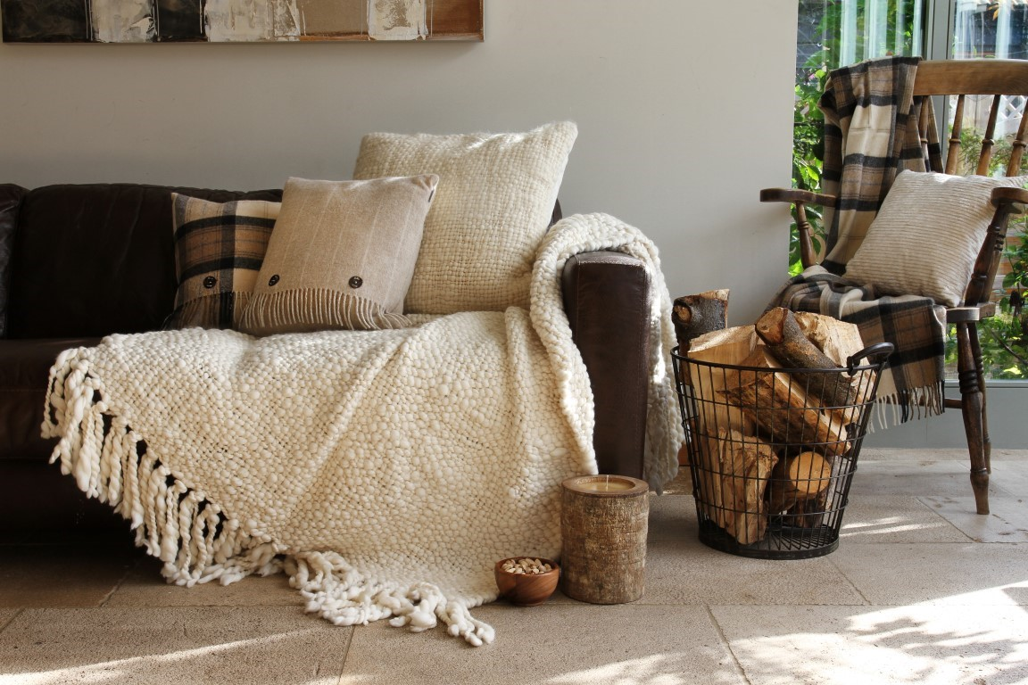 Cosy living room with a sense of hygge and a brown sofa with logs surrounding