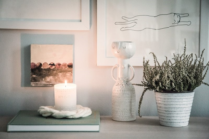a white desk filled with a green book, burning candle, plant pot and white vase as a sense of hygge