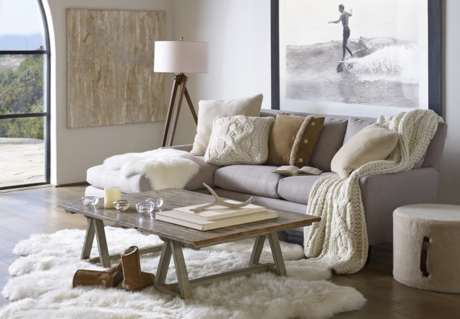 hygge is presented in a large white room comprised of a light grey sofa, white rug, wooden table and other accent accessories