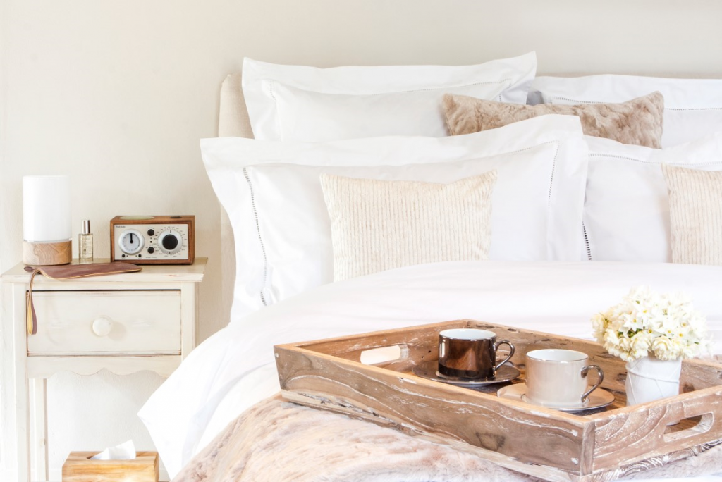 hygge in a white king size bed with a breakfast wooden tray laid upon it and white bedside table next to it