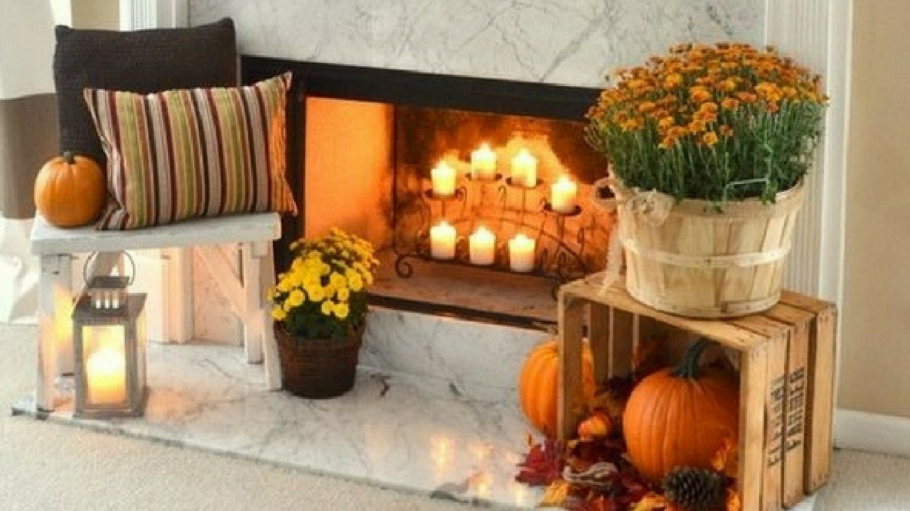 autumn decorations adorning a pale coloured fireplace with pumpkins and orange flowers and autumnal wreaths