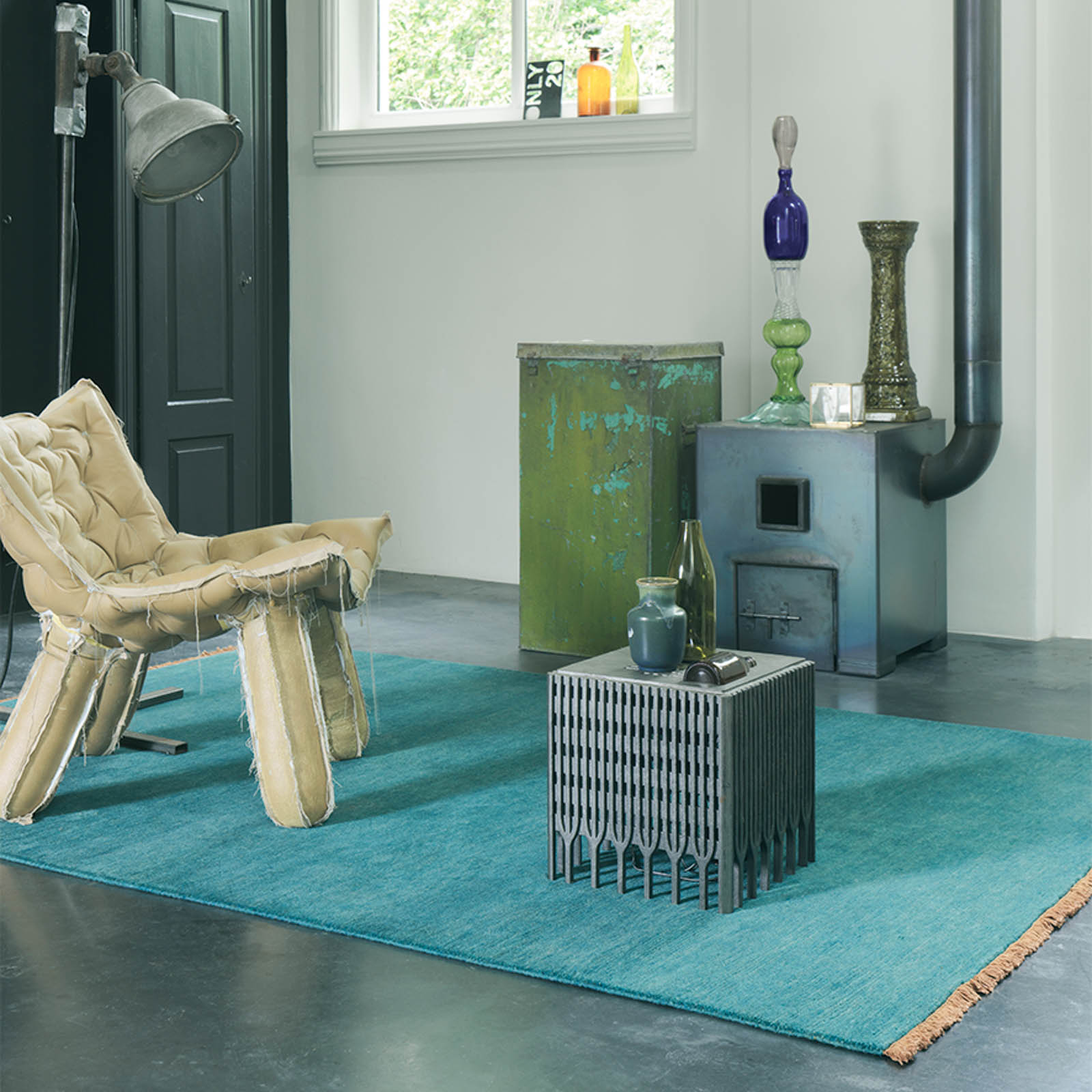 a blue nima rug in a large room with a chair, table and other furniture accents