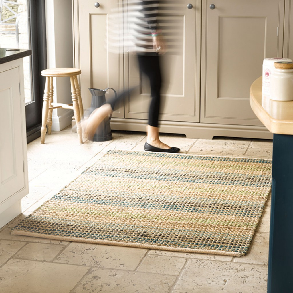a natural fiber rug placed in a kitchen with a lady walking over it - be cautious of foot traffic