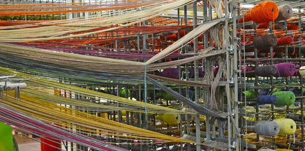 an image showing how a rug is made showing multiple coloured yarns being drawn into a machine loom
