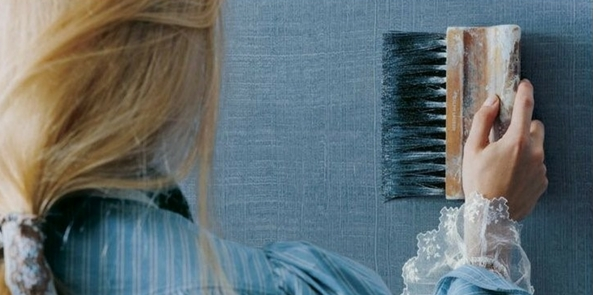 colour trend for 2017 denim blue denim effect wall being demonstrated by brush by blonde woman