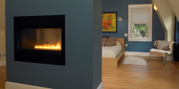 colour trend for 2017 denim blue accent wall with a fireplace in a wooden floored bedroom