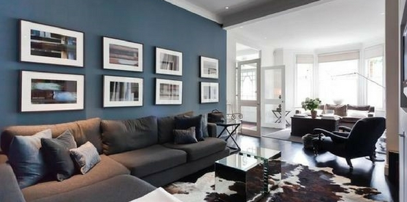 colour trend for 2017 denim blue room with pictures on the wall and a grey sofa in lit room