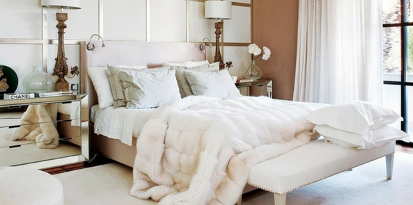 all white style faux fur bedroom with large windows and a white faux fur throw over the end of the white bed