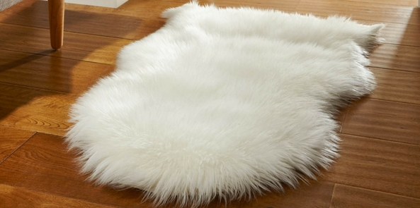sheepskin style faux fur rug on a wooden floor