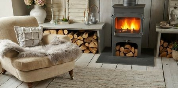 style faux fur in a wooden cabin style room with a roaring fire and neautral coloured rug and armchair with a fur throw