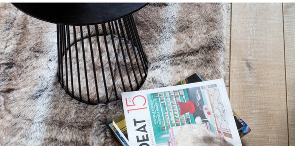 pelle style faux fur rug in brown and grey with a stool and magazines placed on it on a wooden floor