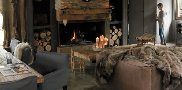 a dark living room with candles and fir with a casual style faux fur throw over the sofa