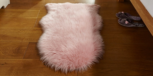 pink style faux fur rug on a brown wooden floor