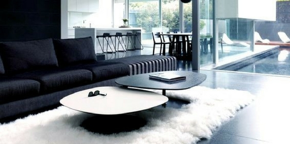 minimalist style faux fur with white rugs under a white and black coffee tables on a black tiled floor next to a black sofa