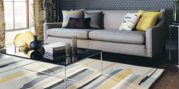 a saffron and grey printed living room rug next to a grey sofa with accented coloured cushions and vases in the room