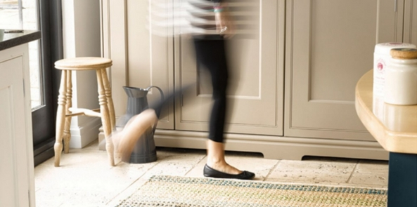 living room rug with a woman walking over a flatweave rug in a brightly lit room
