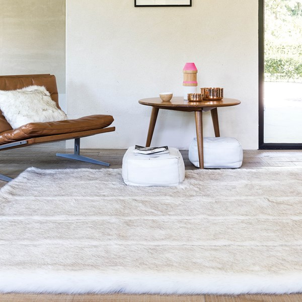 latest rug releases a plush fluffy white rug with a brown leather chair and wooden table