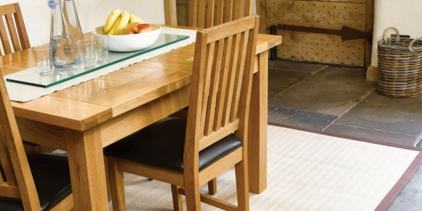 a wooden dining room table of the best kitchen rugs in sisal with a brown border on a dark tiled floor