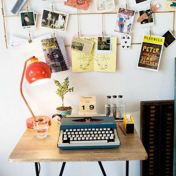 hipster home decor wooden desk with a blue and silver typewriter underneath a bright noticeboard