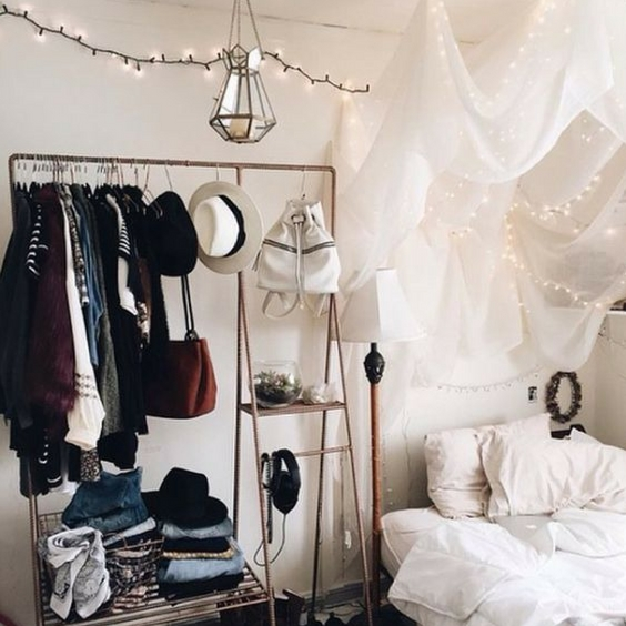 hipster home decor with white walls and fairylights with clothing rail in a bedroom