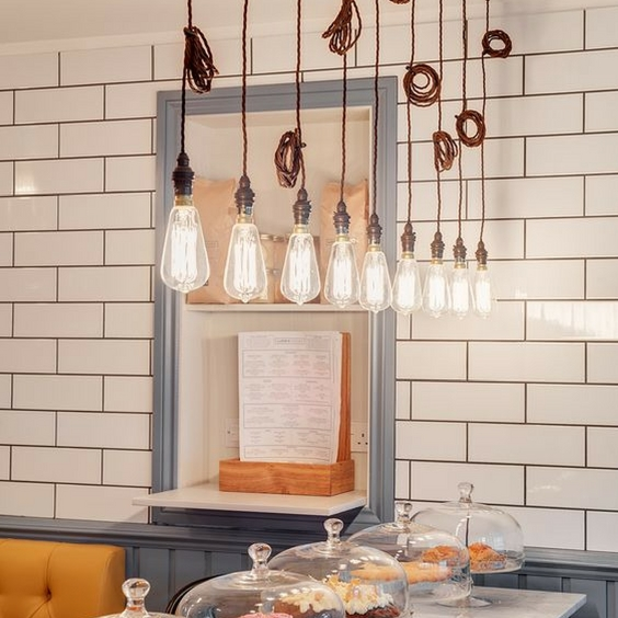 hipster home decor light with vintage lightbulbs hanging from the ceiling above cakes in a tiled cafe