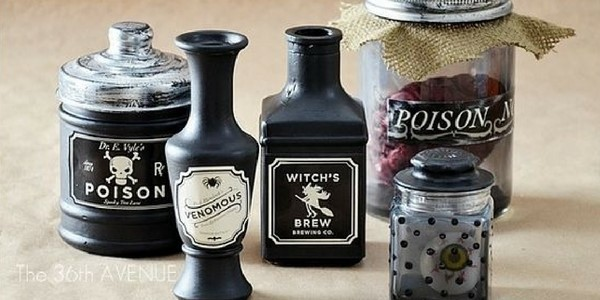 easy diy halloween decorations of poison bottles on a table painted black with apothecary stickers