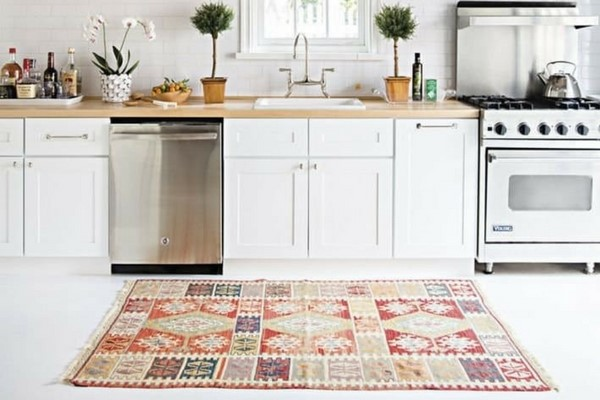 best kitchen rugs in a white kitchen with wooden worksurfaces and vintage patchwork orange rug