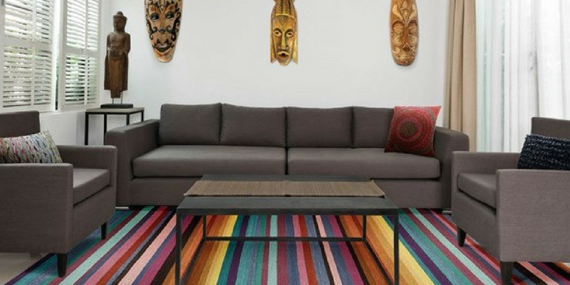stripes trend multicoloured griot rug by kathy ireland in a large living room with grey sofas