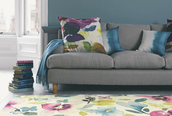 small space with a bright floral rug and a pale grey sofa with legs exposed