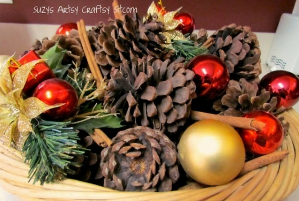 decorative pinecones with pine branches and red and gold baubles and cinammon sticks to help a room smell like christmas