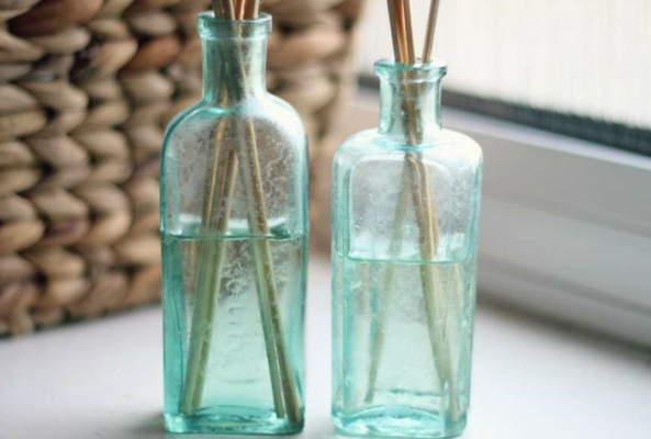 homemade reed diffusers in a blue bottle on a bright windowsill to help a room smell like christmas