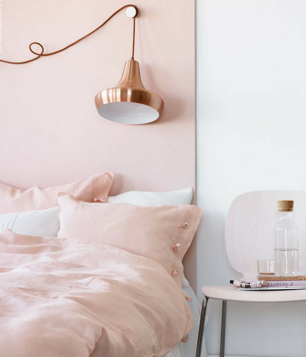 blush pink bedroom with a copper lighting accessory