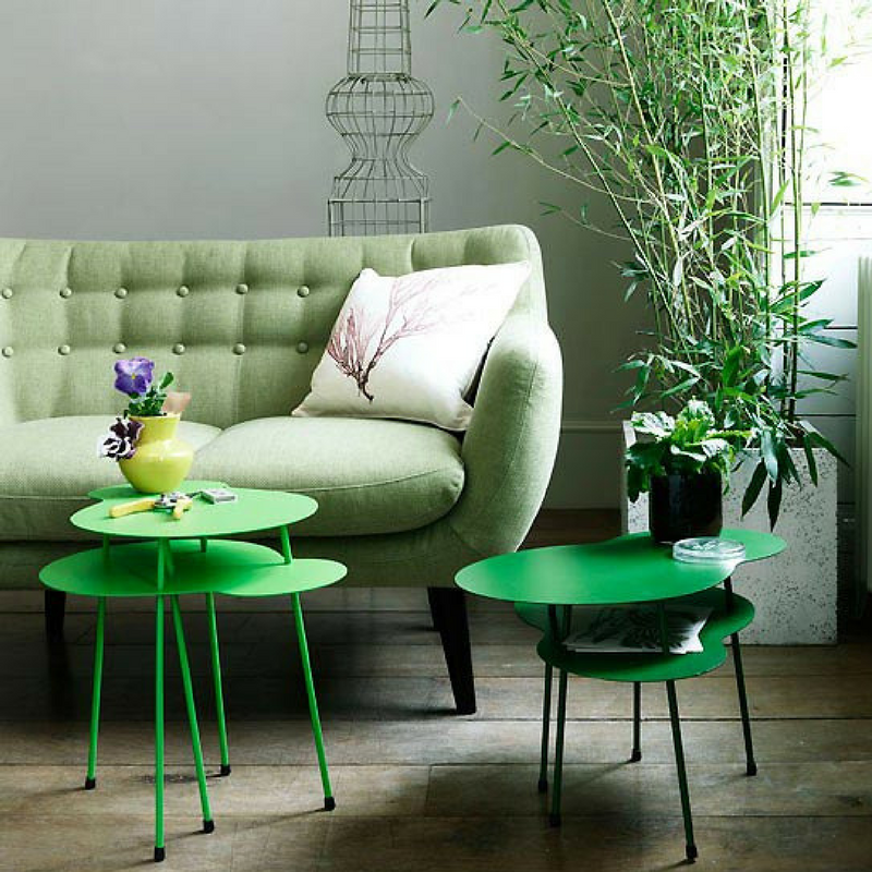 green coloured living room with bold green coffee tables