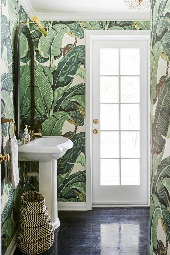 a small bathroom covered in green botanical wallpaper