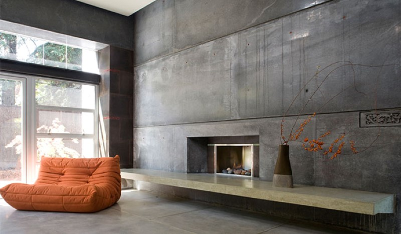 concrete interior with concrete accent wall, fireplace and orange sofa